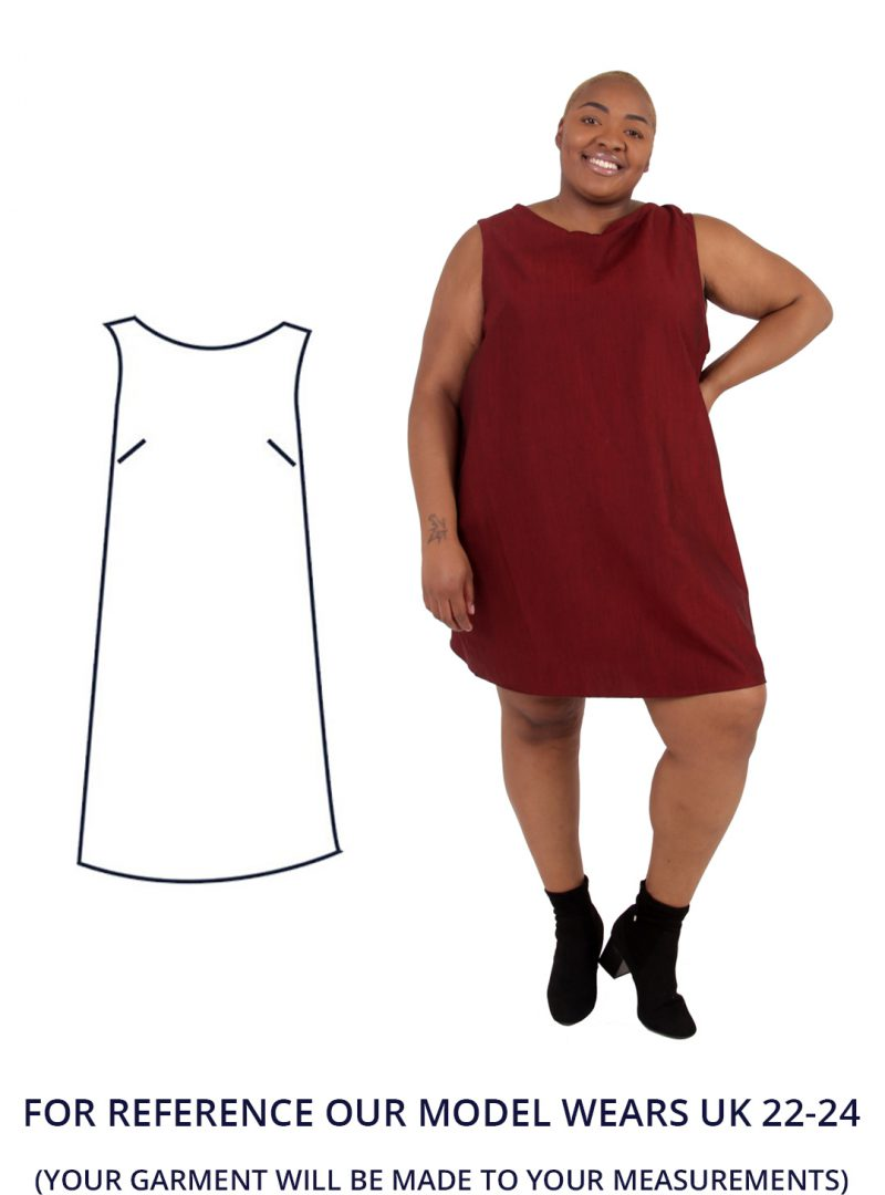 Our model Nyome wears a lovely deep red shift dress. Nyome is stood with one hand on their hip.