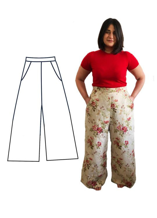 Our model Fenia is stood with their hands in their pockets of their floral wide leg trousers. Fenia is wearing a bright red t-shirt and is barefoot.