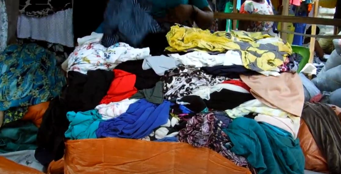 Screenshot of a still from the Dead White Man's Clothes Trailer on YouTube. Image shows a pile of clothes.