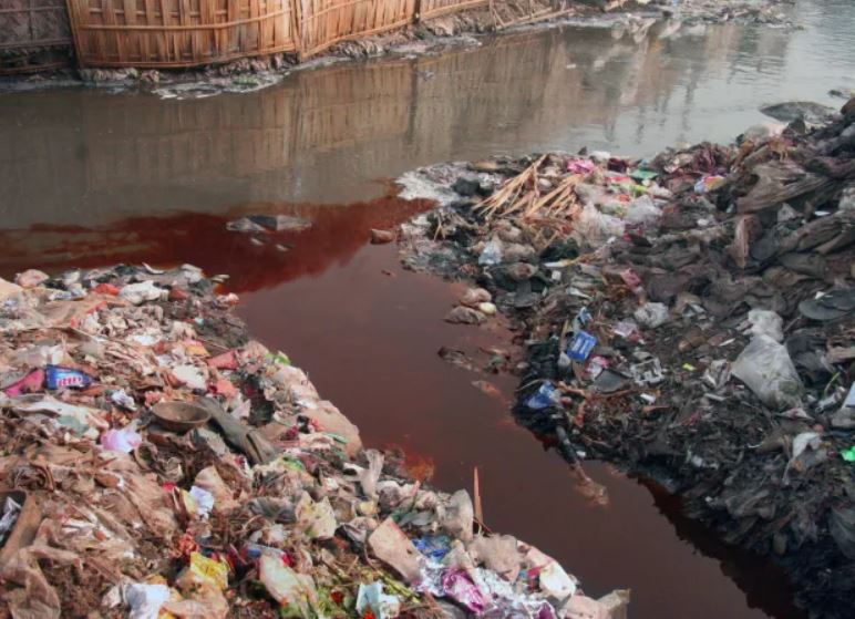 Image of fabric dye being dumped in a river.